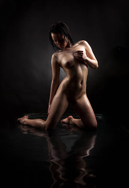 Naked girl in water on a black background stock photo