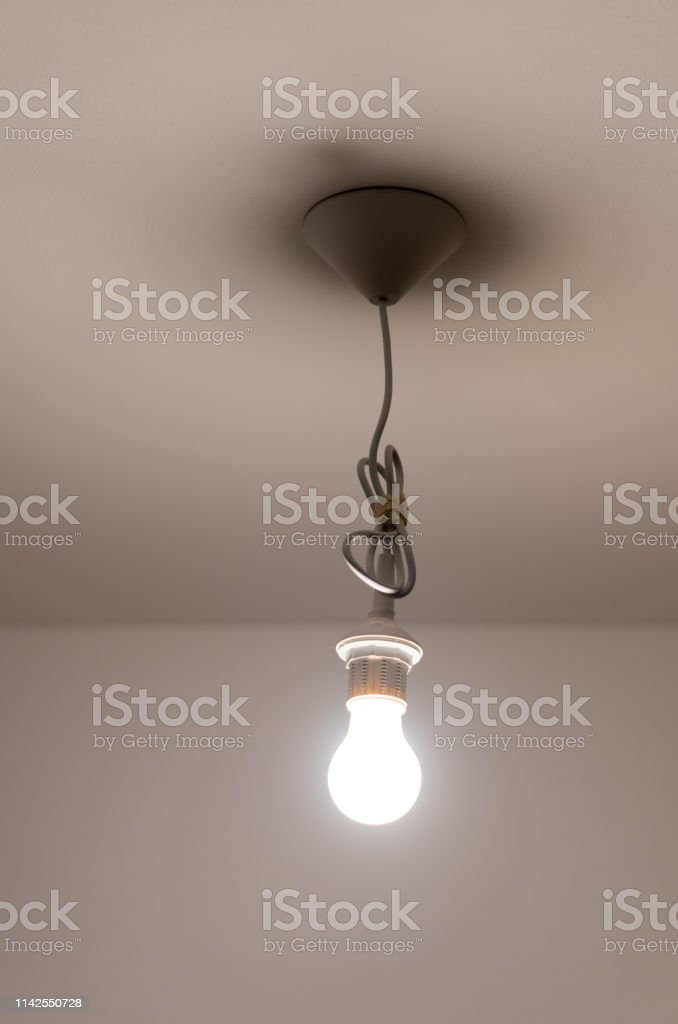 A naked lit light bulb hanging from the ceiling of a dimly lit room