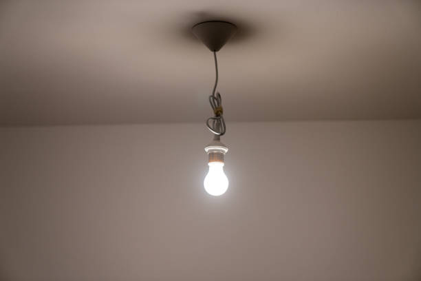 naked lit light bulb hanging from the ceiling of a dimly lit room - dimly stock pictures, royalty-free photos & images