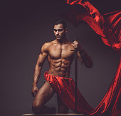 Artistic image with naked muscular man in a red fluttering dress.