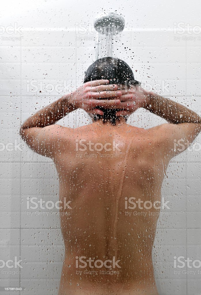 Naked man is taking a shower in bathroom, rear view stock photo