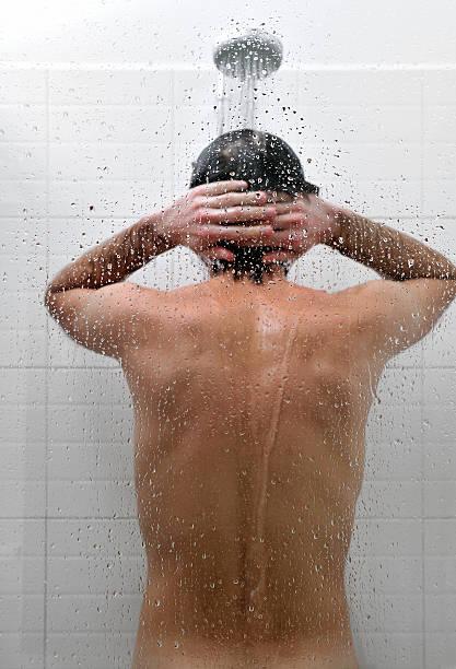 nackt mann nimmt eine dusche im badezimmer, rückansicht - duschen stock-fotos und bilder