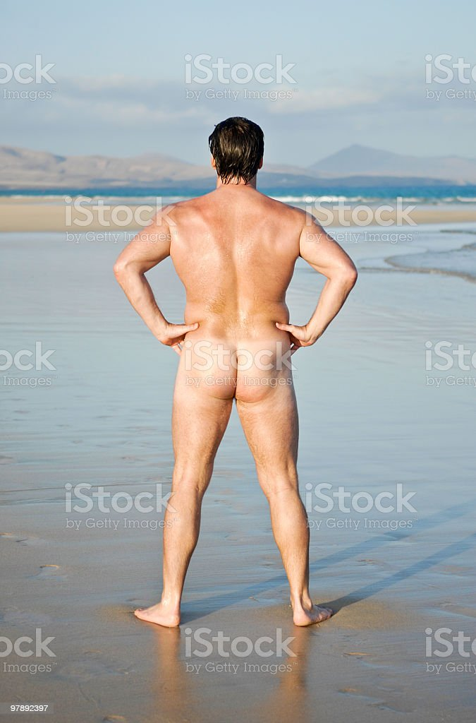 Naked man on sandy beach. royalty-free stock photo