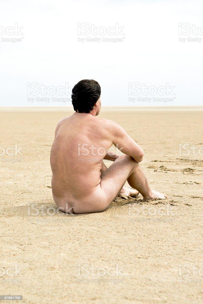 naked man sitting on beach royalty-free stock photo