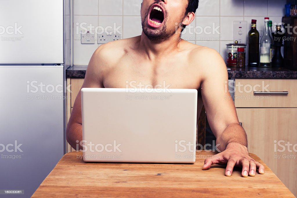 A naked man watching pornography in his kitchen royalty-free stock photo
