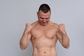 istock Naked mature man clenching fists triumphantly 932874726