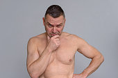 istock Naked mature man with a suspicious expression 932846038