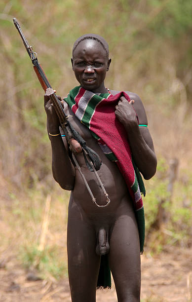 naked mursi man with rifle - indigenous culture stock photos and pictures