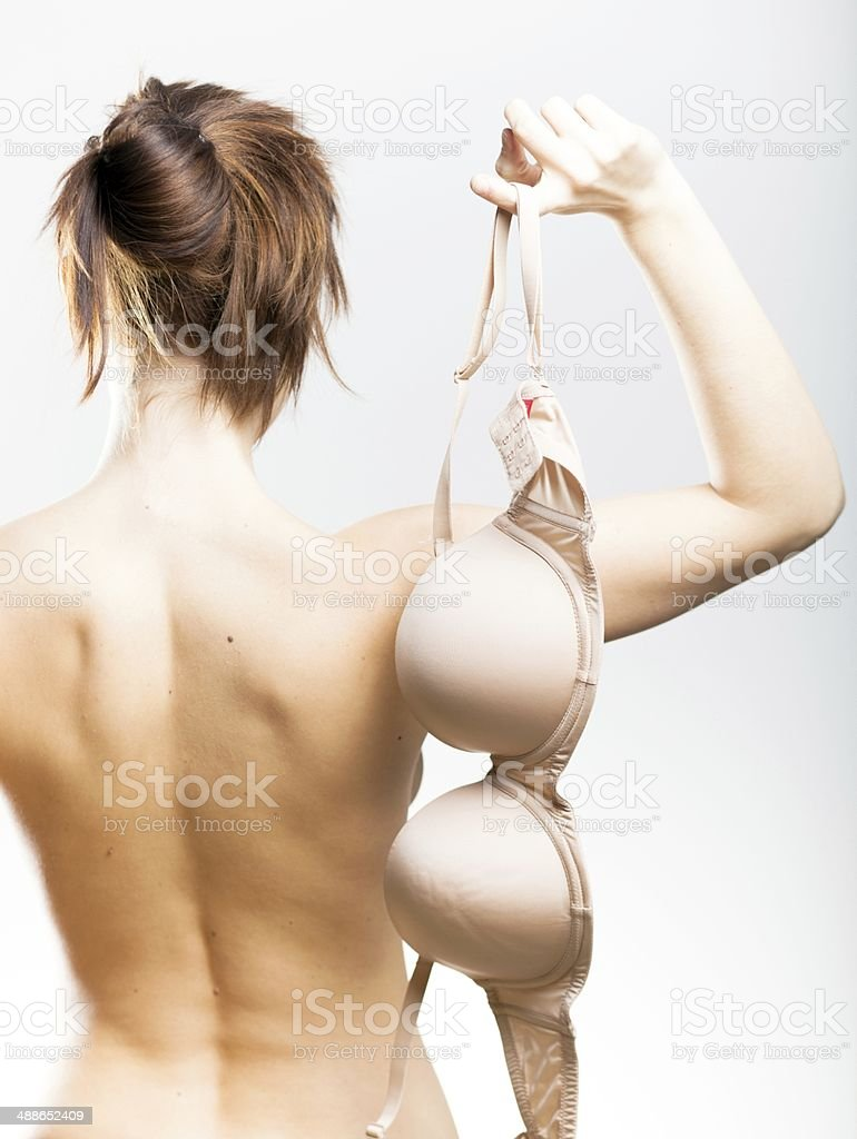 Naked woman back view holding bra in hand stock photo