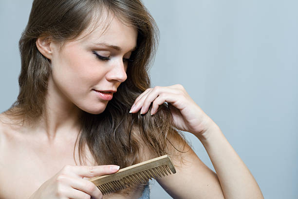 Naked woman combing her long hair with a comb  Attractive woman combing her hair wet hair stock pictures, royalty-free photos & images