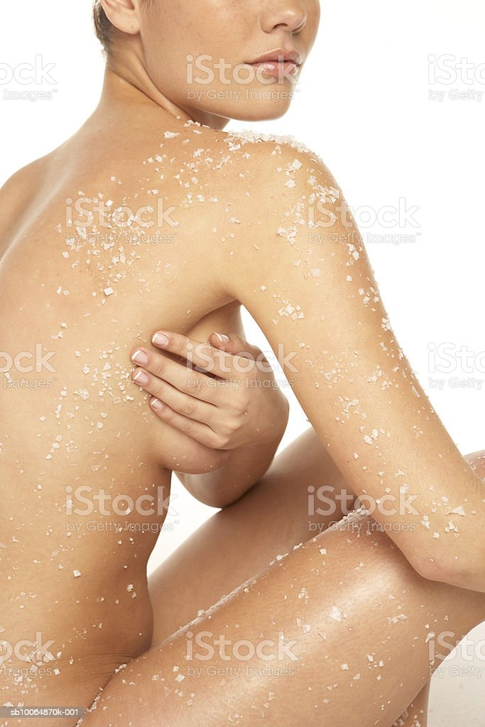 Naked woman covered with rock salt, mid section royalty-free stock photo