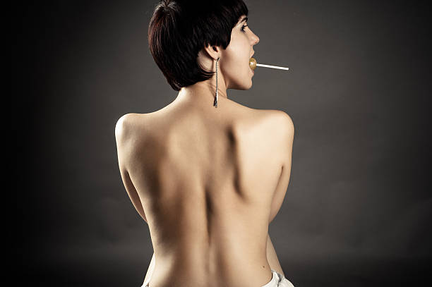 naked woman holding a lollipop in her mouth stock photo