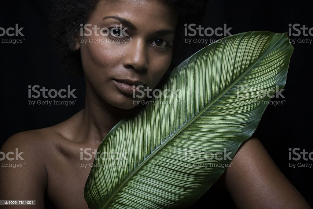 Naked woman holding banana leaf, close-up, portrait photo libre de droits