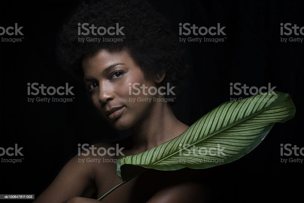 Naked woman holding banana leaf, close-up, portrait royalty-free stock photo
