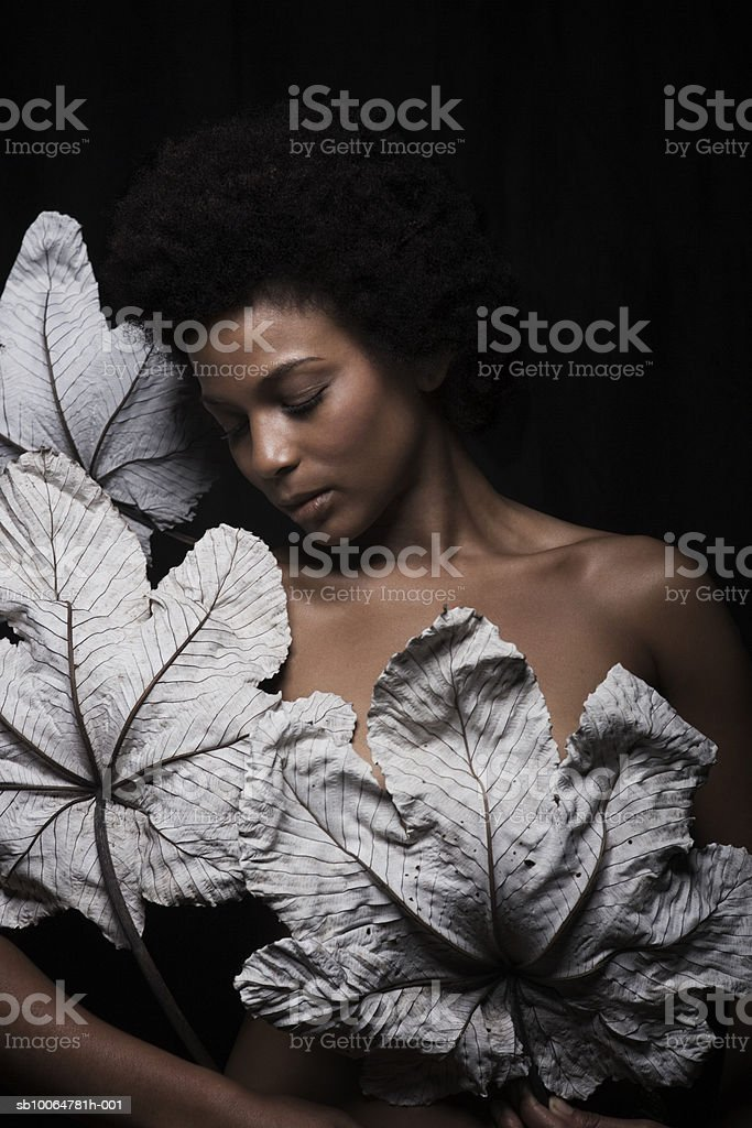 Naked woman holding dry leaves, close-up foto de stock libre de derechos