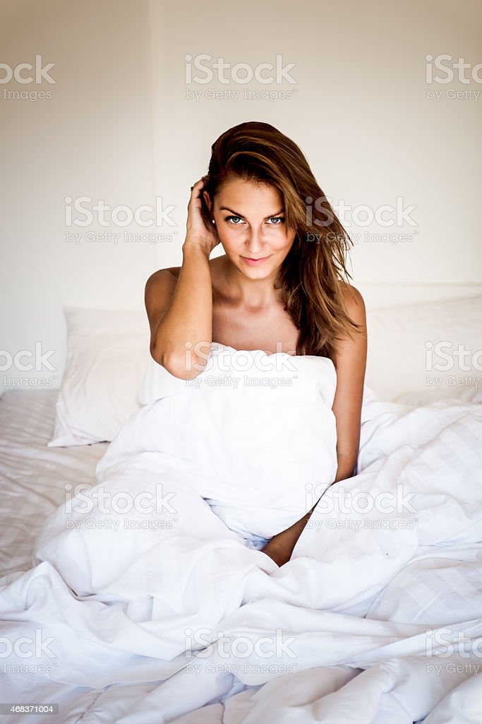 Naked Woman On A Bed Wrapped In A White Sheet Stock Photo