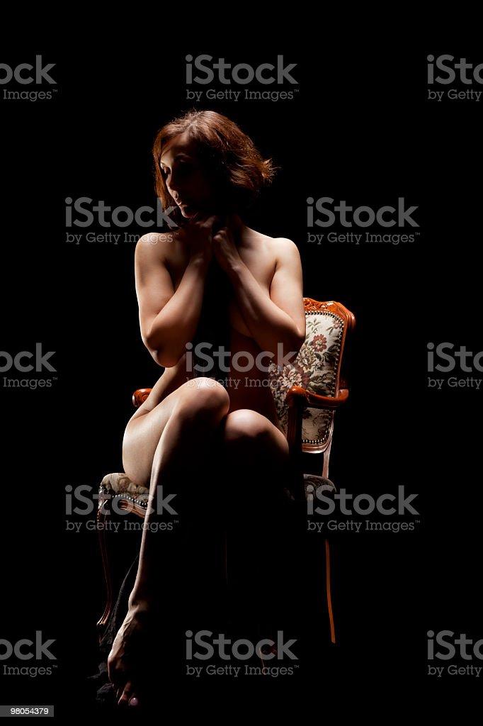 Nudo di donna seduta sulla sedia vecchio foto stock royalty-free