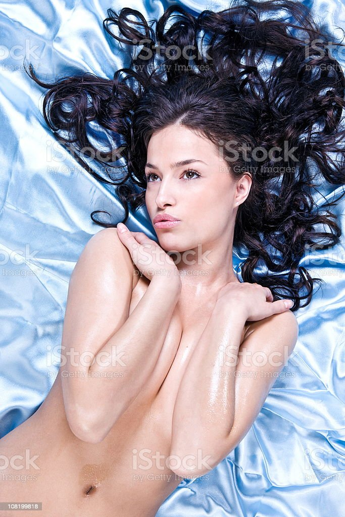 Naked Young Woman Lying on Bed Pouting royalty-free stock photo