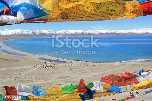 Viewed through prayer flags from a nearby hill, crowds gather on the shores of Nam Tso lake, surrounded by Himalayan peaks, near Lhasa in the Tibet autonomous region of China.