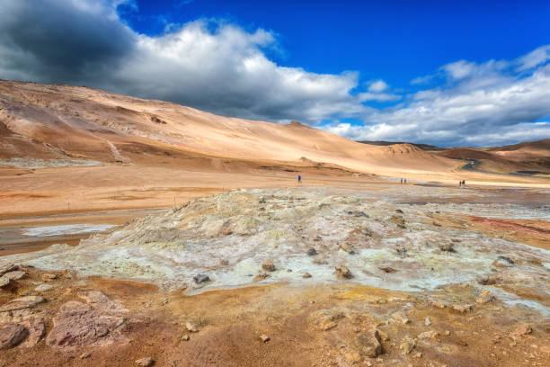 Das Geothermie-Gebiet Namafjall Hverir in Island. Atemberaubende Landschaft des Schwefeltals mit rauchenden Fumarolen und blauem bewölktem Himmel, Reisehintergrund – Foto