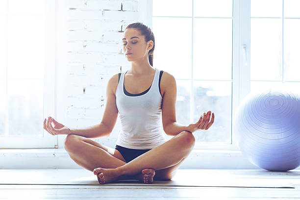 Namaste! Young beautiful young woman keeping eyes closed while sitting in lotus position in front of window at gym lotus position stock pictures, royalty-free photos & images