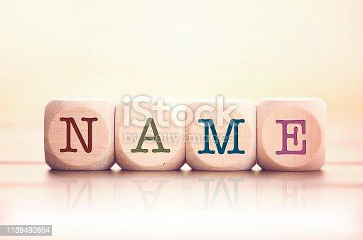 Name word written on cube wooden blocks. Defocused background.