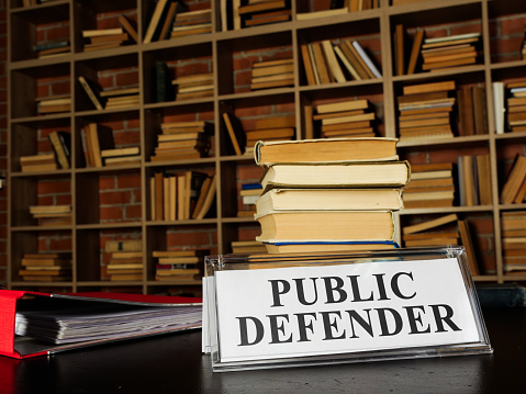 Nameplate public defender and stack of book.