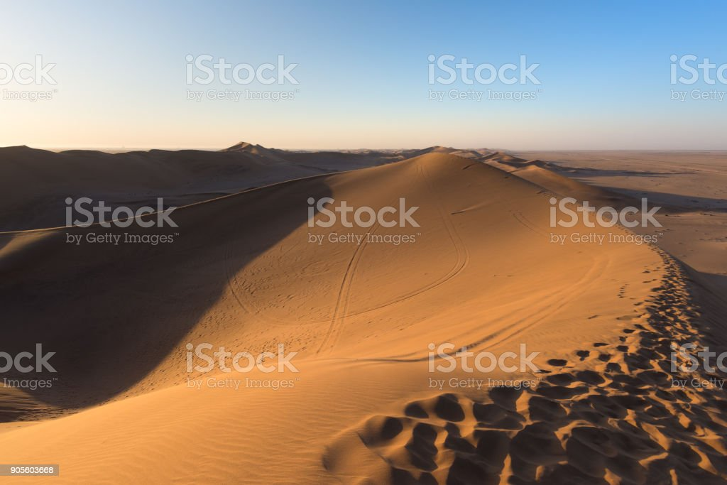 Namib desert, sand dunes footprints, scenic ridge at sunset, Sossusvlei, Swakopmund, Namib Naukluft National Park, travel destination in Namibia, Africa. stock photo