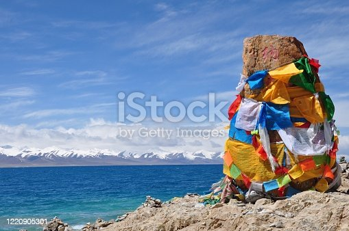 The sign of Namtso wrapped by prayer flags near the lake.