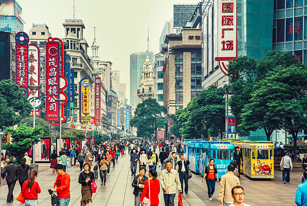Nanjing Road in Shanghai, China Crowds walk below neon signs on Nanjing Road. The street is the main shopping district of the city and one of the world's busiest shopping districts.  shanghai stock pictures, royalty-free photos & images