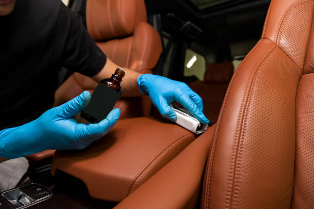 汽車座椅棕色內飾皮革上的納米陶瓷塗層,由一名工人用海綿和瓶子戴藍色手套圖像檔