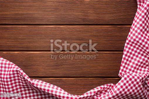 Napkin in a red and white cage on a wooden background, texture, copy space