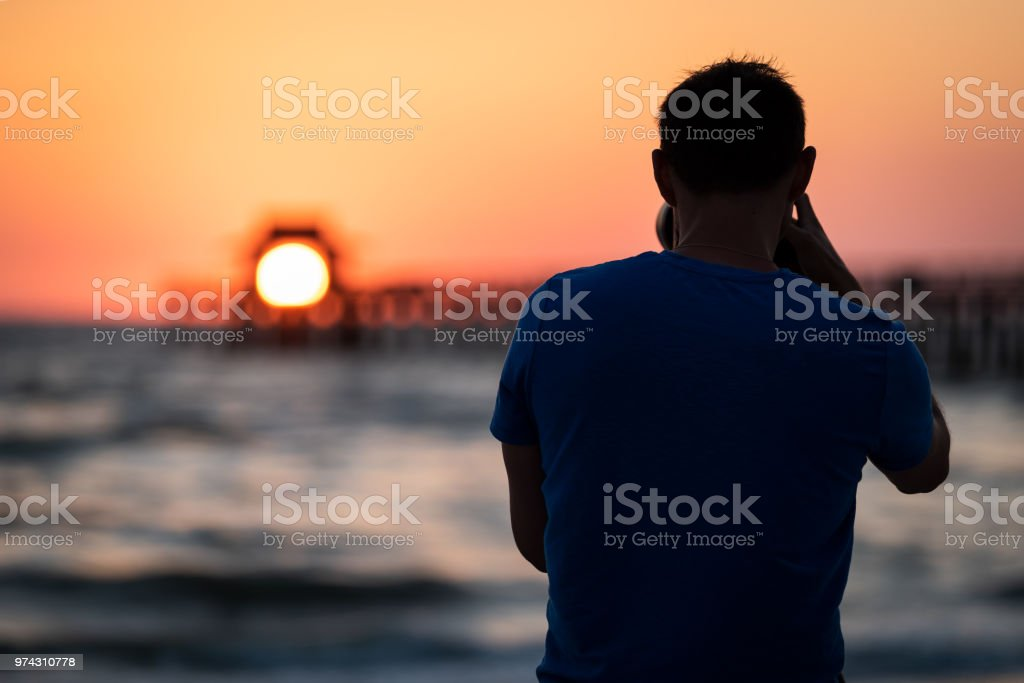 Naples, Florida pink, red and orange sunset in gulf of Mexico with sun setting inside Pier bokeh, back of young man photographer videographer taking pictures filming landscape stock photo