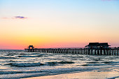 Naples, Florida sunset dusk in gulf of Mexico with pier wooden jetty on horizon and silhouette ocean waves view