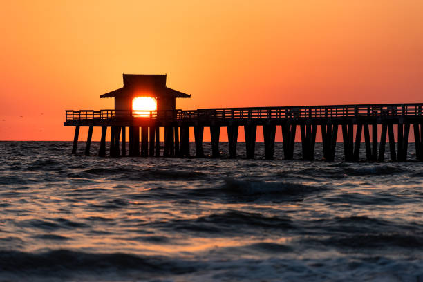 Naples, Florida vibrant orange sunset, in gulf of Mexico with sun peeking in behind Pier wooden jetty, with horizon and dark silhouette ocean waves Naples, Florida vibrant orange sunset, in gulf of Mexico with sun peeking in behind Pier wooden jetty, with horizon and dark silhouette ocean waves naples florida stock pictures, royalty-free photos & images