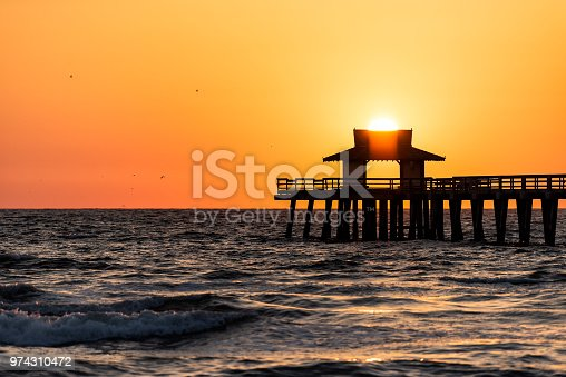 Naples, Florida yellow and orange sunset closeup in gulf of Mexico with sun setting inside Pier wooden jetty, with many birds silhouette flying over horizon and dark blue ocean waves