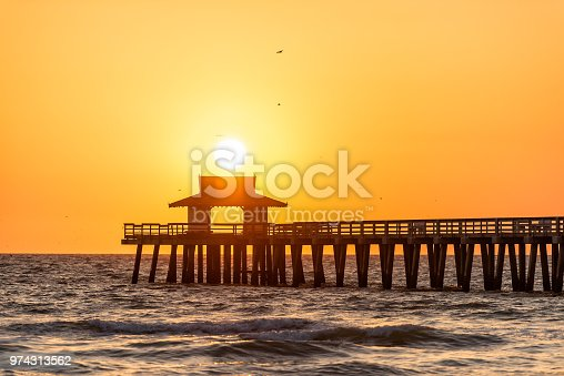 Naples, Florida yellow and orange sunset in gulf of Mexico with sun setting inside Pier wooden jetty, with many birds silhouette flying over horizon and dark blue ocean waves