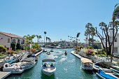 Long Beach, CA - July 14, 2018: waterway canal in the Naples Island neighborhood of Long Beach, California showing homes and people in boats enjoying a summer day