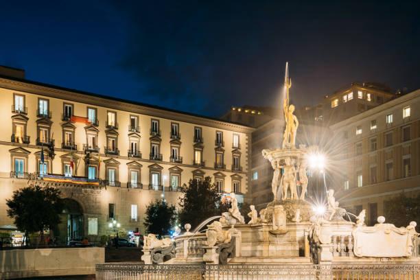 Naples, Italy. Fountain Of Neptune On Piazza Municipio In Evening Or Night Illuminations stock photo