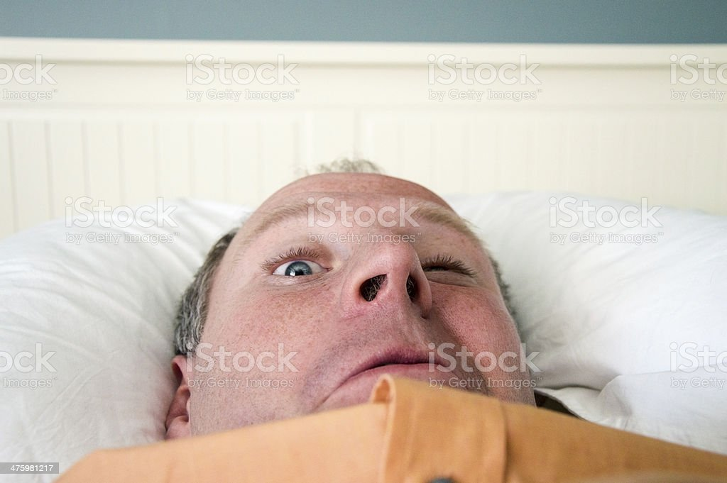 Napping businessman with one eye opened stock photo
