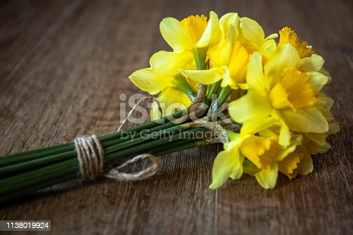 Bouquet of yellow narcissus flowers on wooden table