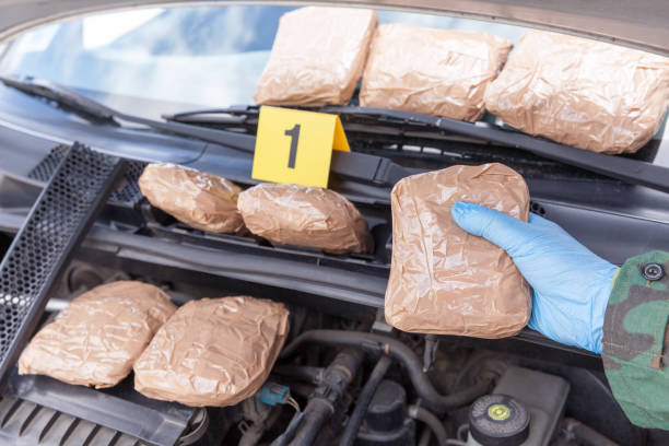 Narcotic smuggling: Hidden drug packages discovered in engine compartment of a car Police officer holding drug package discovered in engine compartment of a car smuggling stock pictures, royalty-free photos & images