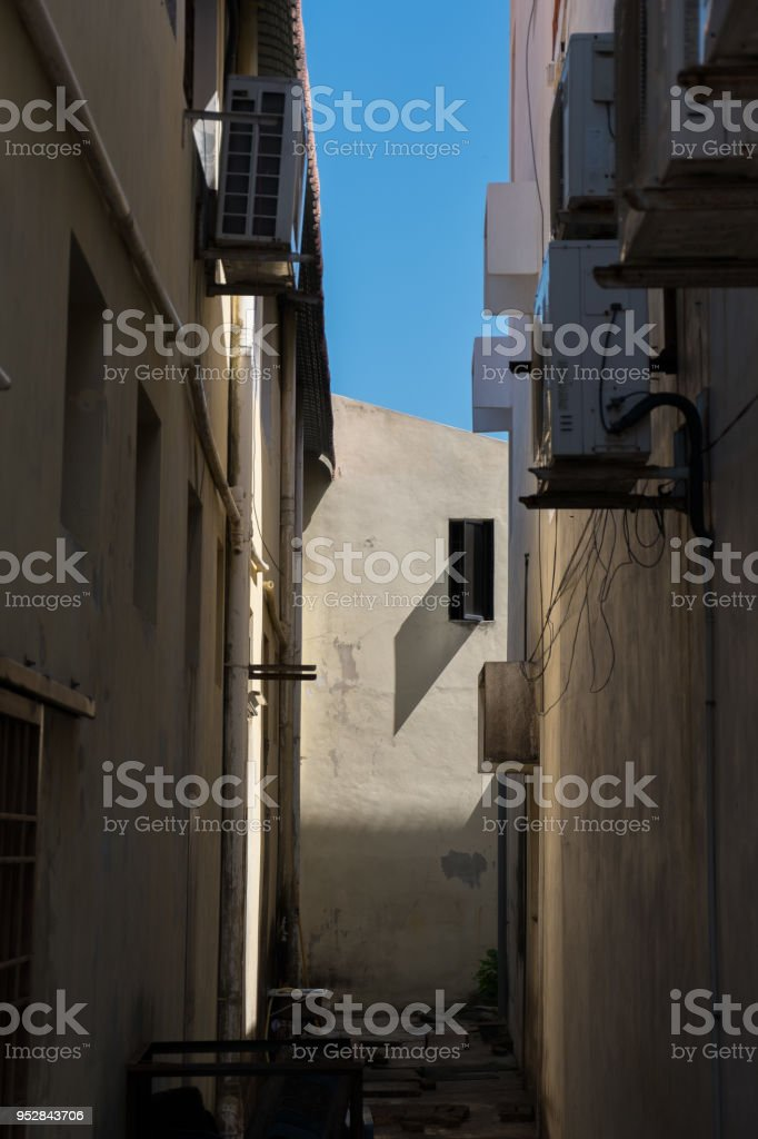 Narrow alley with air conditioner units and sun stock photo