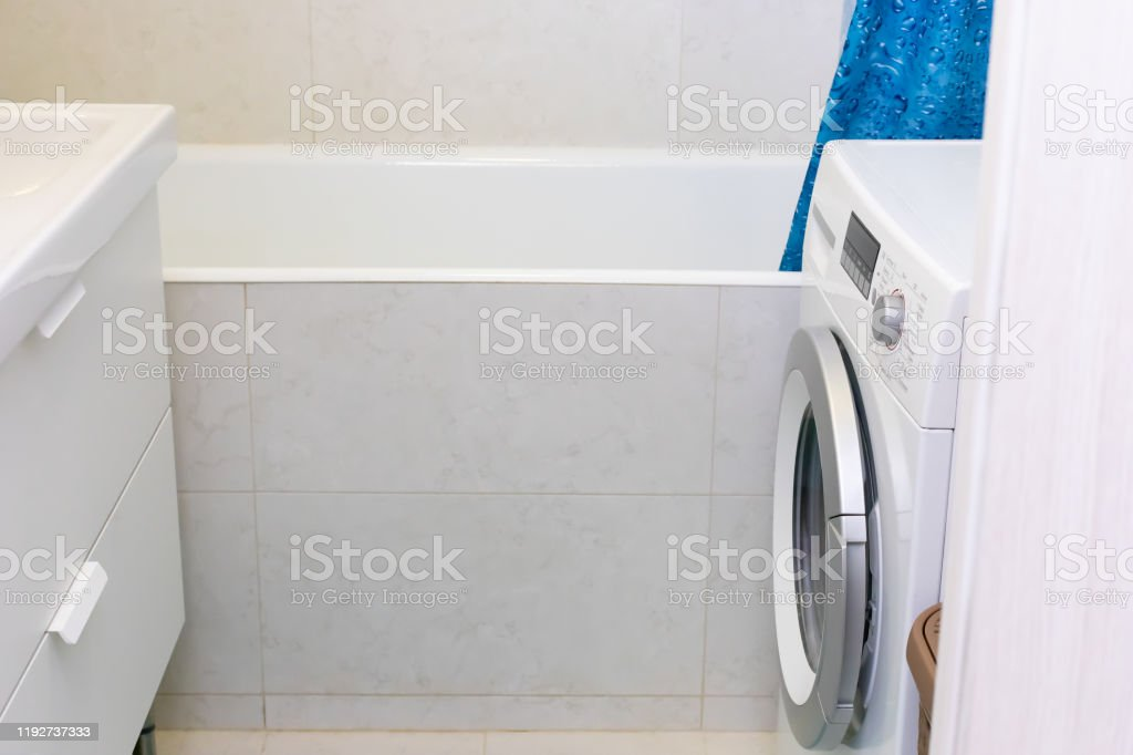 Narrow Bathroom In A Small Apartment Decorated With White Marble Tiles Covered With A Pedestal A Castiron Bathtub A Washing Machine With A Silver Drum Stock Photo Download Image Now Istock