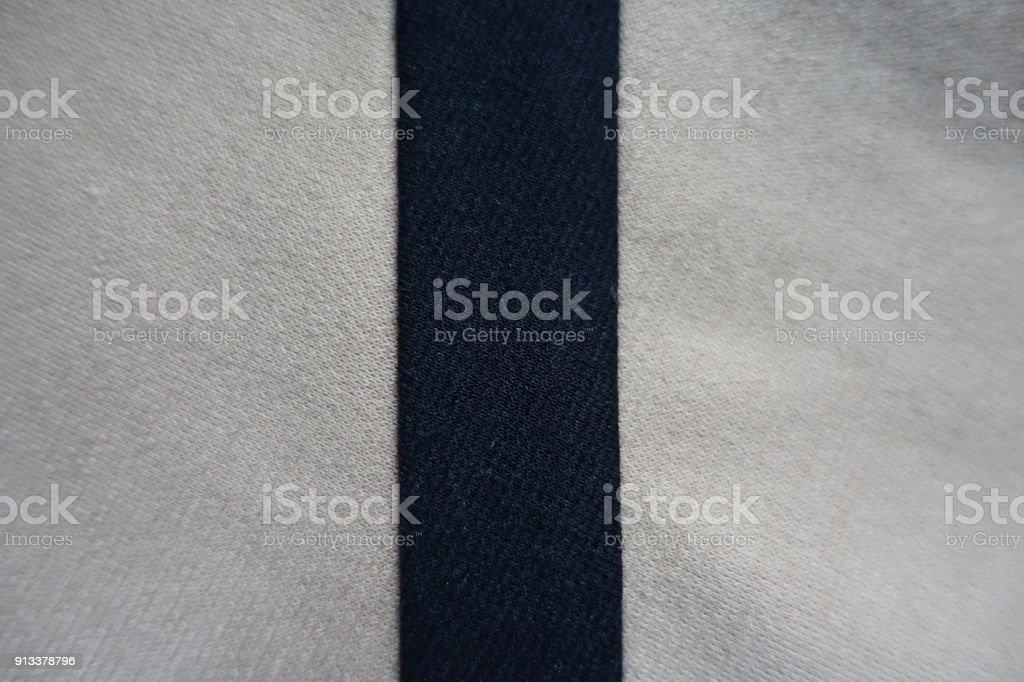 Narrow black ribbon sewn to beige fabric vertically stock photo