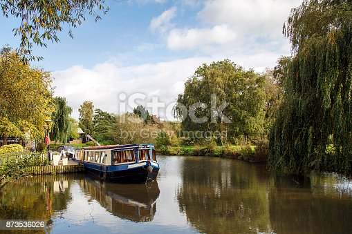 Picturesque landscape of a narrow boat moored on the Avon river awaiting tourists to cruise down the river through Stratford upon Avon, England