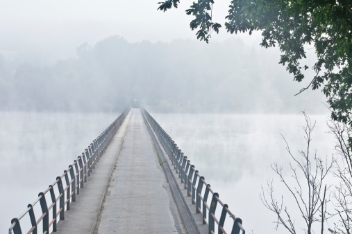 Long narrow bridge over a lake on a quiet misty morning