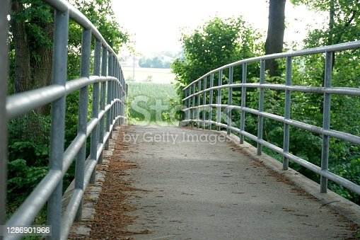 A narrow bridge with metal railings on both sides surrounded by lush green vegetation diminishing in the perspective of a sun flooded land. A photo with copy space and potentially symbolic meaning.