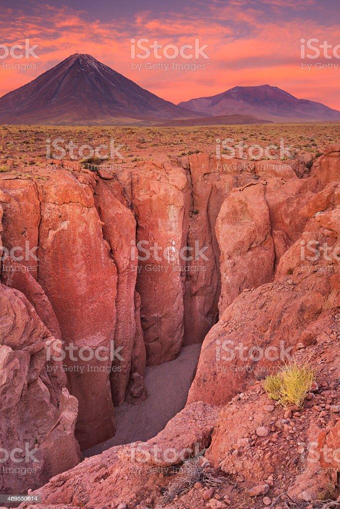 Narrow canyon and Volcan Licancabur, Atacama Desert, Chile at sunset stock photo