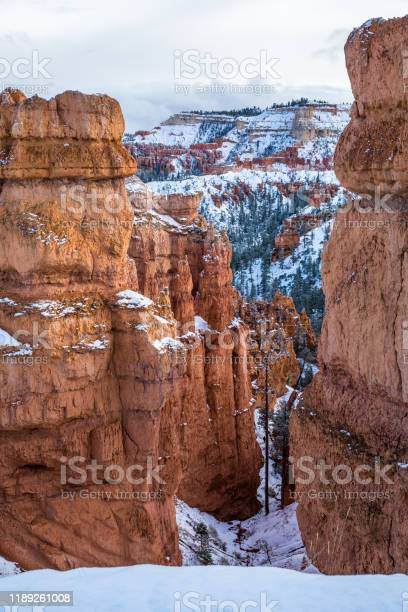 Photo of Narrow canyon through orange sandstone cliffs after winter snow in Bryce Canyon, Utah